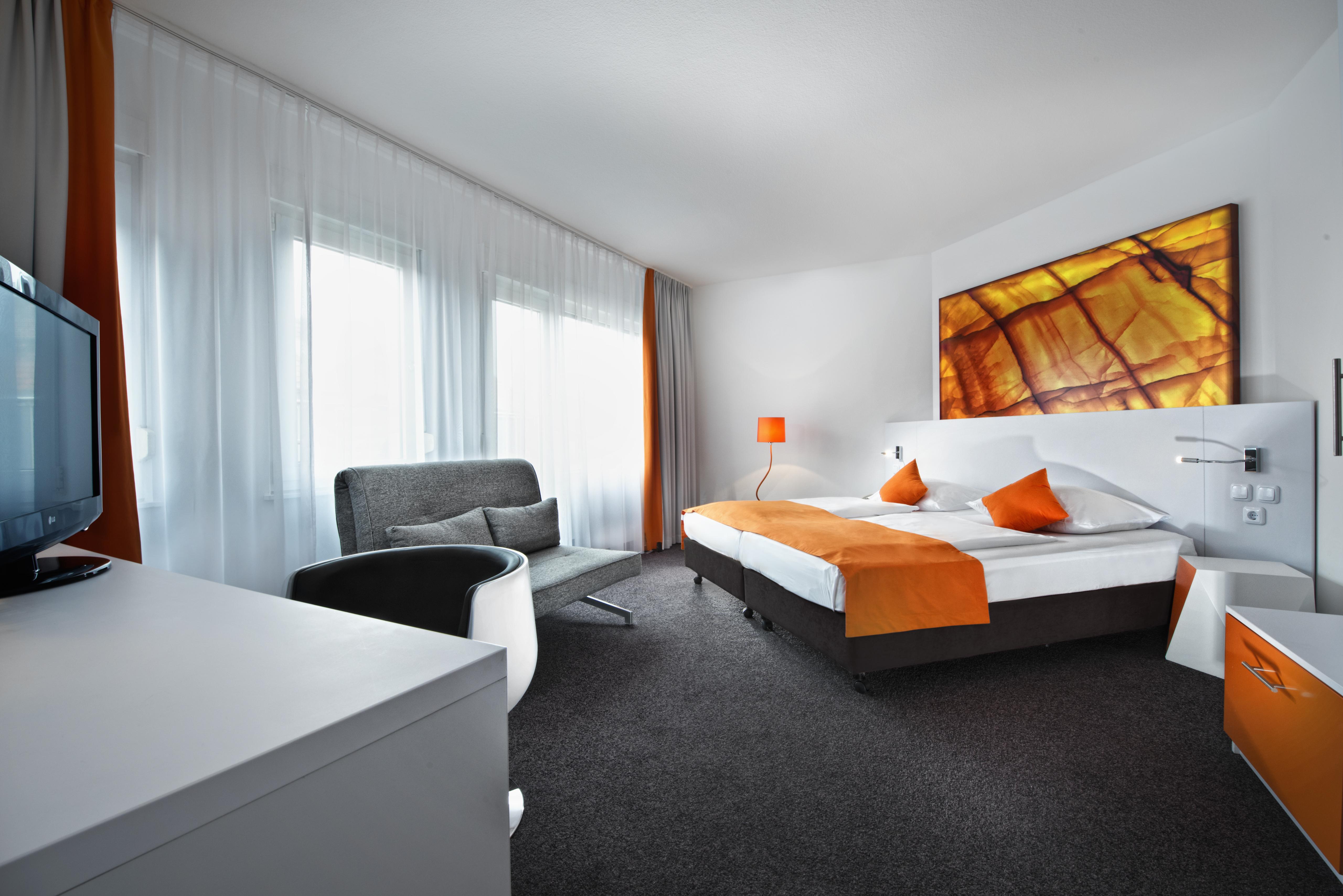 satndard double room with orange interior in dsseldorf city centre hotel wyndham garden dsseldorf - Wyndham Garden